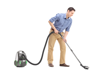 vacuum cleaning: Studio shot of a cheerful young man using a vacuum cleaner isolated on white background Stock Photo