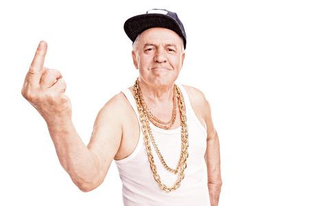 Senior man met een hip-hop cap en een gouden ketting, die de vinger en kijken naar de camera op een witte achtergrond Stockfoto