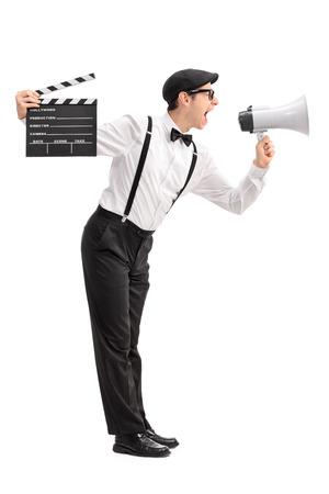 megafono: Perfil de cuerpo entero foto de un director de cine joven sosteniendo una claqueta y gritando en un meg�fono aislado en el fondo blanco