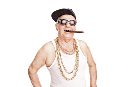 in chains: Desdentado mayor con un casquillo de hip-hop y una cadena de oro alrededor de su cuello que fuma un cigarro aislado en fondo blanco