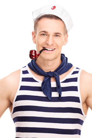 Vertical shot of a young sailor smoking tobacco from a brown pipe and looking at the camera isolated on white background photo
