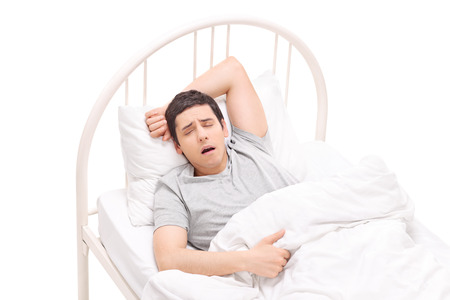 bad feeling: Young man sleeping in a bed and having nightmares isolated on white background