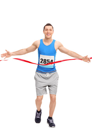 marathon runner: Full length portrait of a male runner with a race number on his chest, crossing the finish line isolated on white background