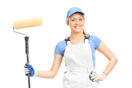 painter girl: Female house painter in a white uniform posing with a paint roller isolated on white background