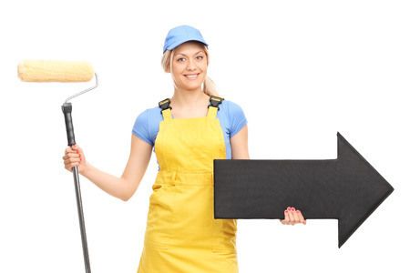 painter: Female painter in a yellow uniform holding a paint roller and a big black arrow pointing right isolated on white background