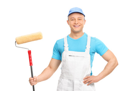 decorator: Male decorator posing with a paint roller isolated on white background Stock Photo