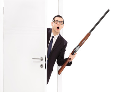gun room: Angry businessman in a black suit holding a shotgun rifle and entering a room isolated on white background Stock Photo