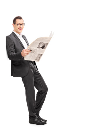 Full length portrait of a happy young businessman reading a newspaper and leaning against a wall isolated on white background photo