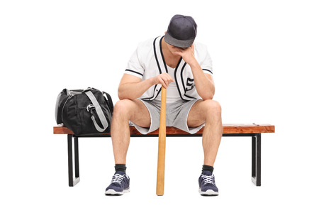 head down: Sad young baseball player sitting on a bench and contemplating with his head down isolated on white background Stock Photo