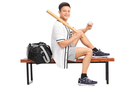 player bench: Baseball player holding a baseball bat, sitting on a wooden bench and looking at the camera isolated on white background