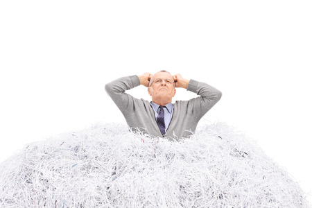 stuck: Senior man stuck in a pile of shredded paper, gesturing anger isolated on white background