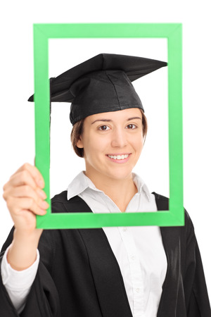 yearbook: Vertical shot of a female student posing in graduation gown behind a green picture frame isolated on white background Stock Photo