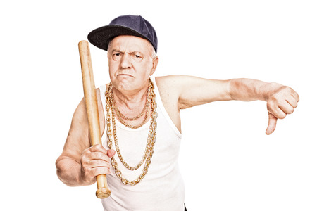 baseball sport: Violent senior in hip-hop clothes holding a baseball bat and giving a thumb down isolated on white background