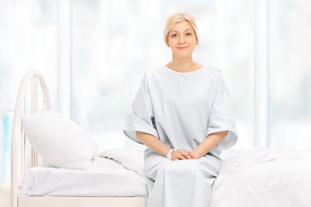 hospital gown: Blond female patient posing seated on a hospital bed and looking at the camera
