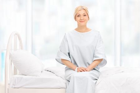 mujer en la cama: Paciente femenina rubia posando sentada en una cama de hospital y mirando a la cámara