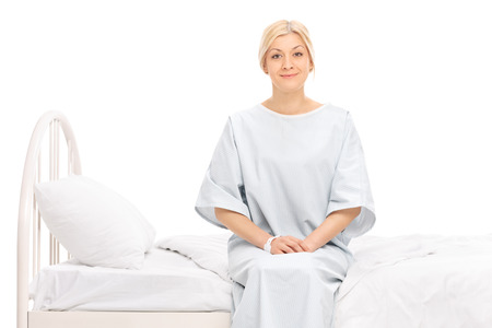 recovery bed: Blond female patient sitting on a hospital bed and looking at the camera isolated on white background Stock Photo