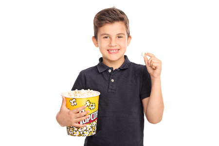 Joyful kid holding a big box of popcorn and looking at the camera isolated on white background