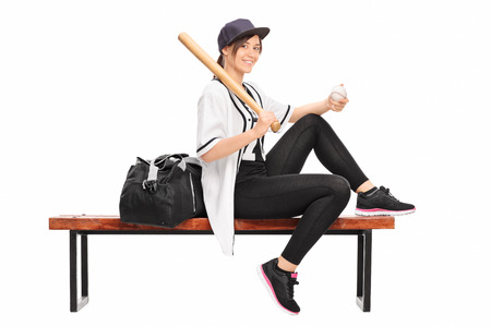 Female baseball professional holding a baseball bat seated on a bench with a black sports bag beside her isolated on white background photo