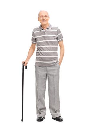 Retrato de cuerpo entero de un anciano en una camisa polo informal sosteniendo un bastón y posando aislado sobre fondo blanco. Foto de archivo