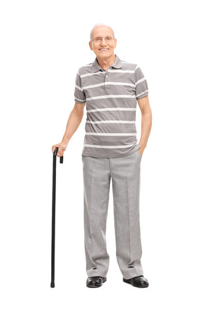 Full length portrait of an old man in a casual polo shirt holding a cane and posing isolated on white background Stockfoto