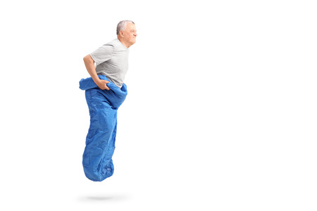 Senior man jumping in a blue sack and smiling isolated on white background