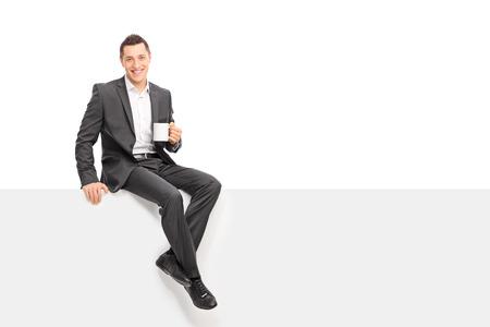 グレーのスーツのコーヒー カップを保持していると白の背景に分離されたブランク パネルの上に座って青年実業家