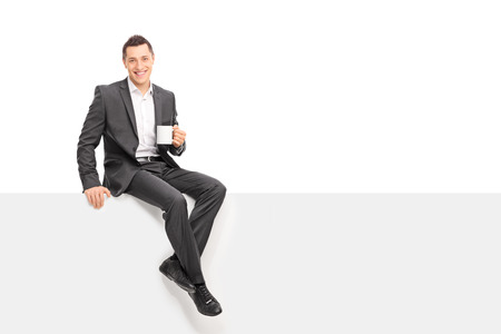 Young businessman in a gray suit holding a cup of coffee and sitting on a blank panel isolated on white background Stock Photo