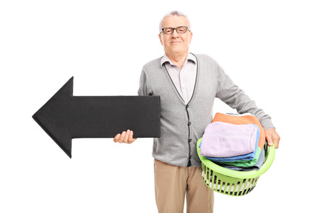 launder: Senor gentleman holding a laundry basket full of clean clothes and a big black arrow pointing left isolated on white background