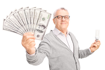 Economic senior holding an energy efficient light bulb and a stack of money isolated on white background