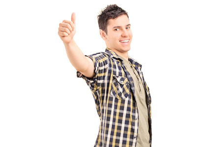 posing  agree: Relaxed young guy giving a thumb up isolated on white background