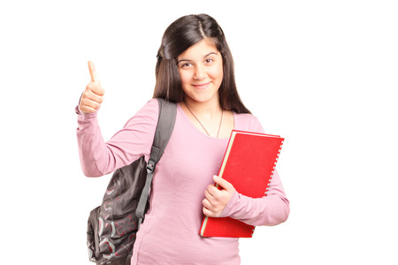 posing  agree: Teenage schoolgirl giving a thumb up isolated on white background
