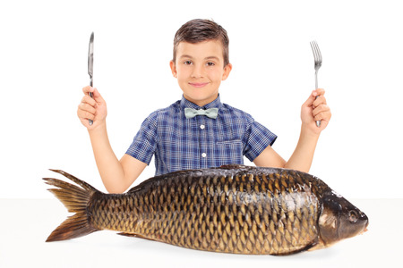 eater: Little kid holding a fork and a knife seated at a table with a huge raw fish in front of him isolated on white background