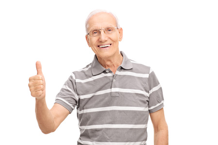 posing  agree: Cheerful senior man giving a thumb up and looking at the camera isolated on white background