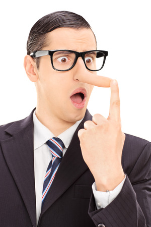 cheater: Vertical shot of a young displeased businessman looking at his long nose and trying to put it back with his finger isolated on white background Stock Photo
