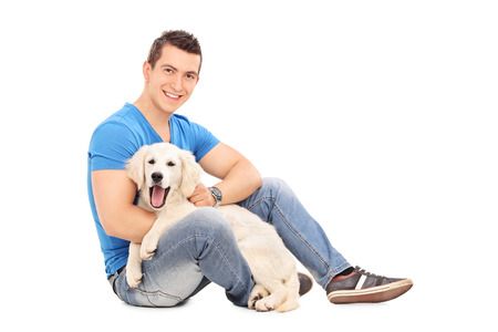 man dog: Cheerful young man posing with a cute little Labrador puppy and looking at the camera isolated on white background