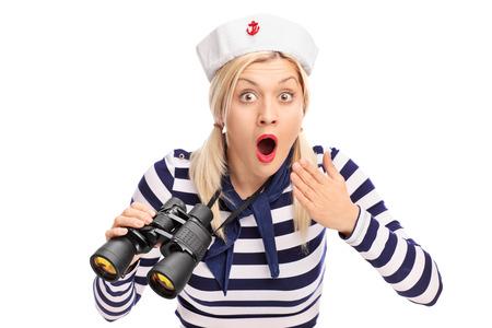 Zaskoczony kobiet żeglarz gospodarstwa lornetki i patrząc na kamery na białym tle