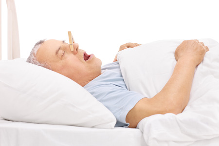 snoring: Senior sleeping in a bed and snoring with a clothespin stuck on his nose isolated on white background
