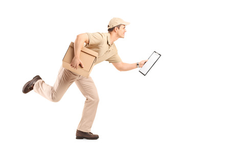 Full length portrait of a delivery guy running with a cardboard box and a clipboard in his hands isolated on white background photo
