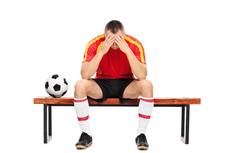 player bench: Worried young football player sitting on a wooden bench with his head down isolated on white background Stock Photo