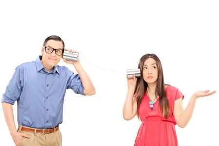 Pares jovenes que hablan a través de un teléfono lata. La mujer es un gesto de confusión y el hombre está sonriendo y escuchando cuidadosamente aislado en fondo blanco