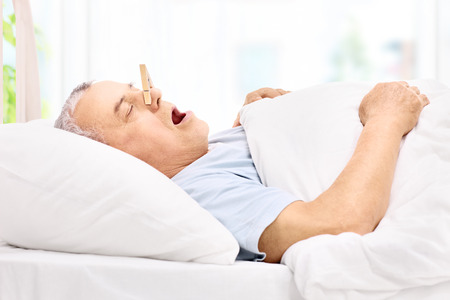 snoring: Senior man sleeping with a clothespin on his nose and snoring at home