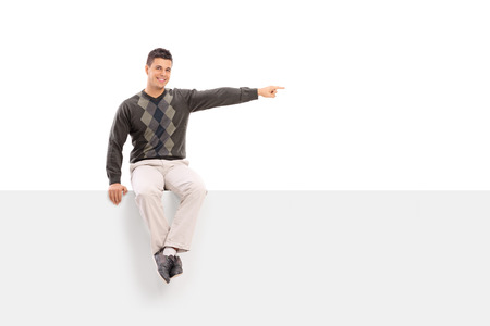 blank billboard: Casual young man sitting on a blank signboard pointing with his hand and looking at the camera isolated on white background Stock Photo