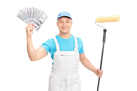 decorator: Cheerful young decorator holding a paint roller and a stack of money isolated on white background Stock Photo