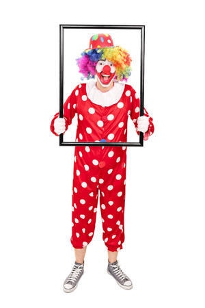 big picture: Full length portrait of a male clown holding a big picture frame and posing behind it isolated on white background