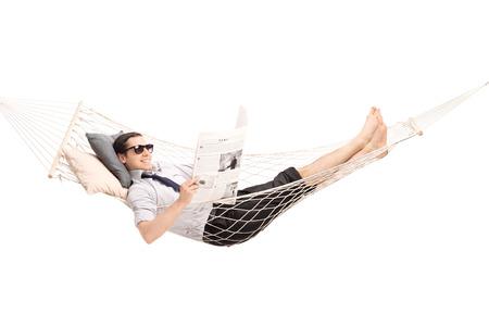 periodicos: Relajado joven leyendo un periódico y acostado en una hamaca cómoda aislado en fondo blanco