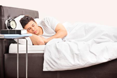 Jovem homem dormindo em uma cama confort�vel coberto com uma manta branca em um quarto Imagens