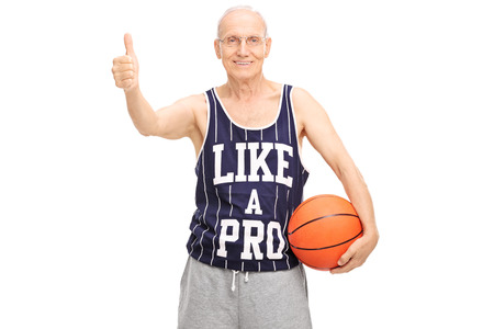 posing  agree: Studio shot of a cheerful senior holding a basketball and giving a thumb up isolated on white background
