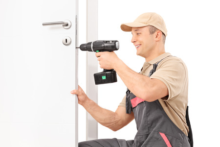 Young male locksmith screwing a screw on a lock of a door with a hand drill isolated on white background Archivio Fotografico