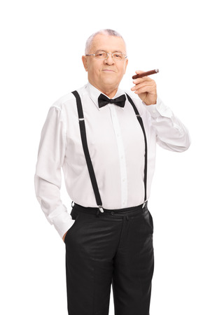 senior smoking: Vertical shot of an elegant senior gentleman smoking a cigar and looking at the camera  isolated on white background Stock Photo
