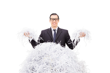 shred: Cheerful businessman holding shredded paper in both hands and smiling isolated on white background